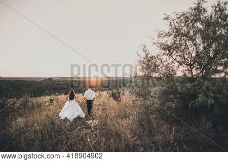 The Groom In White Shirt And Black Trousers Walks By The Hand With Black-haired Curly-haired Bride I