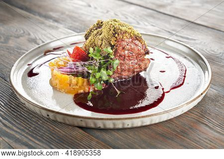 Close Up View Of Beef Meat With Pistachio Topping Served With Cranberry Sauce. Tasty Meal With Fruit