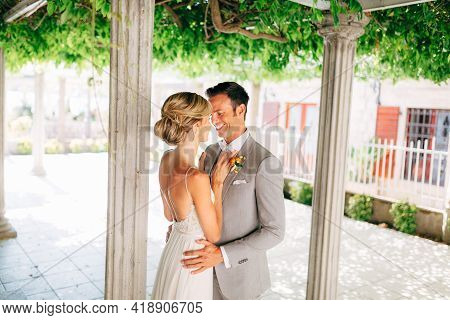 The Bride And Groom Stand Between The Columns, Hugging And Smiling. The Bride Put Her Hands On The G