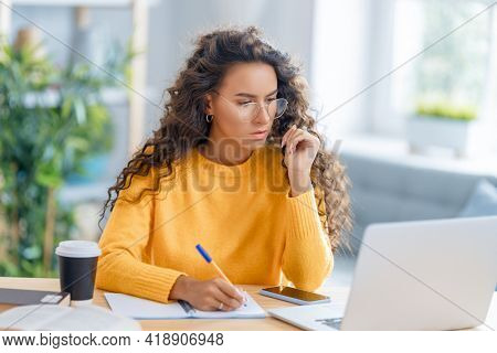 Focused young businesswoman studying online, watching webinar, podcast on laptop, making notes, sitting at work desk. E-learning concept.