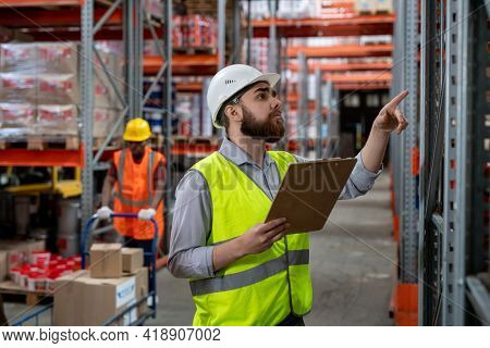 Serious pensive bearded warehouse manager in white hardhat and green vest holding clipboard and counting boxes while inspecting goods