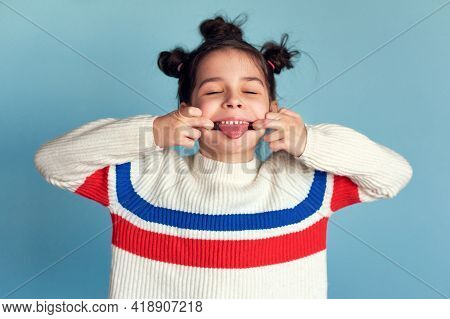 Portrait Of A Funny Little Girl Showing Tongue Having Fun Fooling Isolated Over Studio Blue Color Ba