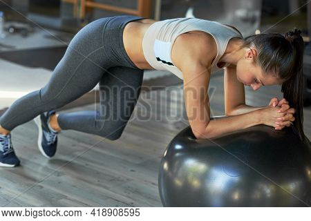 Horizontal Full-length View Of An Athlete Woman Doing Cardio Exercises With A Fit Ball At The Gym. F