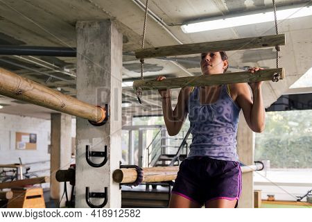 Young Sporty Woman Trains Her Strength By Doing Pull-ups At The Gym, Active And Sporty Lifestyle Con