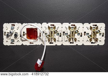 A Network Cable Protruding From The Wall With A Ready Rj45 Module To The Computer Socket In The Room