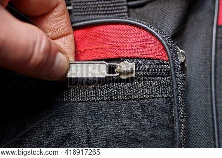 Fingers Hold And Open A Gray Metal Zip On The Black Red Fabric Of The Bag