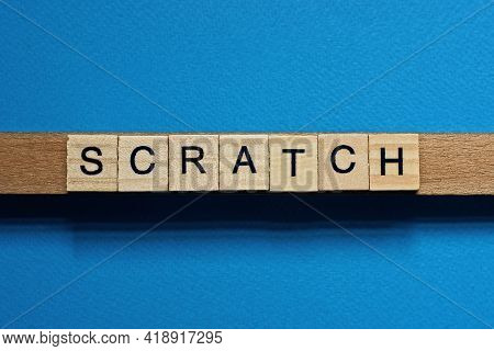 Gray Word Scratch In Small Square Wooden Letters With Black Font On A Blue Background