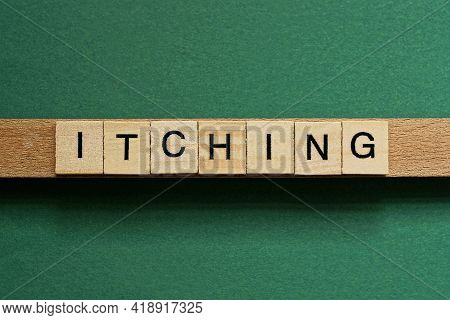 Gray Word Itching From Small Wooden Letters On A Green Table