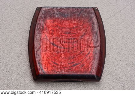One Old Shabby Red Plastic Box Lies On A Gray Table