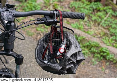 One Gray Bicycle Helmet Hanging On A Black Bicycle Handlebar On The Street In The Park