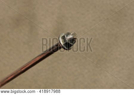 One White Long Metal Bolt With Nut On A Gray Table