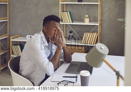 Black Man Sitting At His Office Desk Feeling Tired, Overwhelmed And Stressed Out