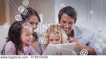 Composition of network of connections with email icons over family using tablet at home. global technology, data processing and digital interface concept digitally generated image.