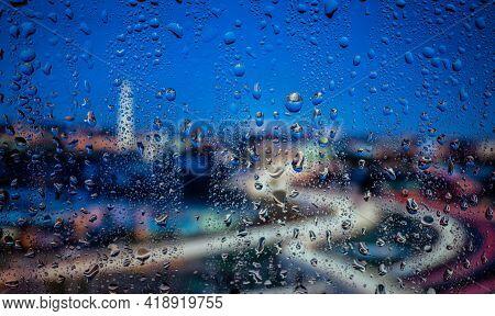 City View Through A Window On A Rainy Night,rain Drops On Window With Road Light Bokeh. Rainy Days.