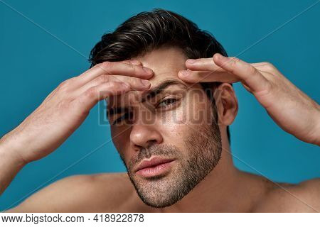 Closeup Portrait Of Shirtless Handsome Guy Checking His Skin, Looking For Blemishes While Posing Iso