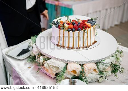 A Beautiful Wedding Cake, Decorated With Fruits, Raspberries, Strawberries And Blueberries. The Bott