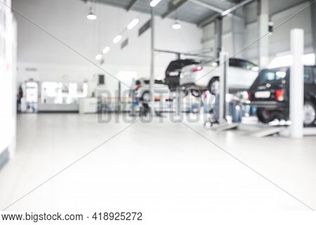 Car Repair Service In Defocus, Industrial Background. Cars On Lifts, Transport Service Area, The Mec