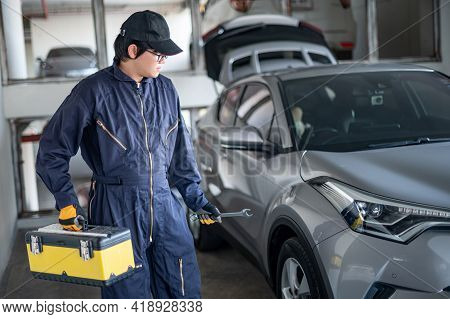 Asian Auto Mechanic Holding Tool Box And Wrench Checking Car In Auto Service Garage. Mechanical Main