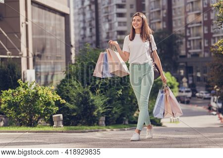 Full Size Photo Of Brown Hair Lady Wear White Cloth Trousers Sneakers Walking In Park Outside Holdin