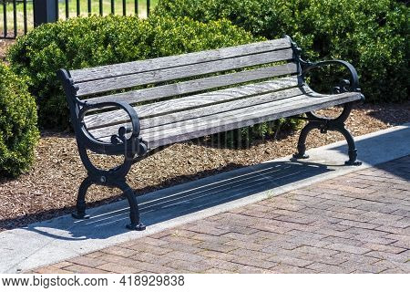 A Comfortable Park Bench That Shows Signs Of Aging.  The Wood Is Gray And The Metal Work Has Lost It