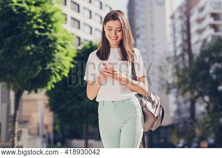 Photo Portrait Of Female Student With Backpack Typing Sms Using Mobile Phone Walking Along City Stre