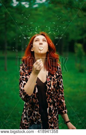 Young Red-haired Woman Blows Away A Dandelion. Beautiful Female In A Fashionable Leopard Print Jacke