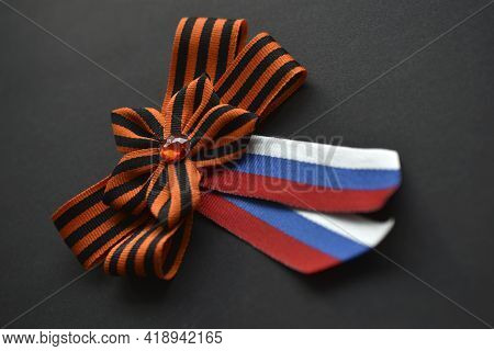 St. George Ribbon And Russian Flag In A Ribbon On Clothes On A Black Background