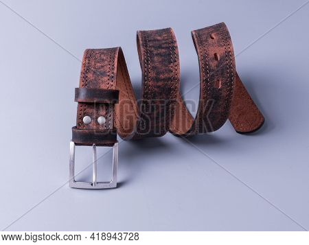 The Belt Is Made Of Genuine Brown Leather With A Worn Texture. Wooden Background Painted With Gray P