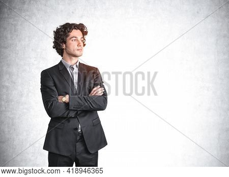 Young Handsome Man Standing With Arms Crossed, Confident Look. Mockup Copy Space Blank Concrete Wall