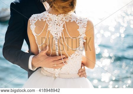The Bride And Groom Are Standing And Hugging On The Pier Near The Sea, Hand Of The Groom On Brides B
