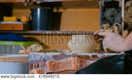 Professional Male Potter Shaping And Carving Pot With Special Tool In Pottery Workshop, Studio. Craf