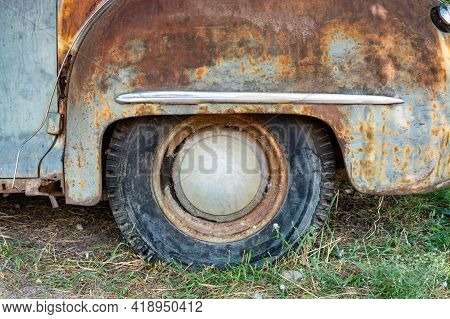 Rear Wheel Of A Rusty Vintage American Car Staying On The Grass