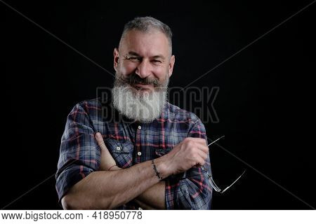 Studio Portrait Of Mature Bearded Man In Casual Clothes With Eyeglasses In Hand Smiles And Looks Dir