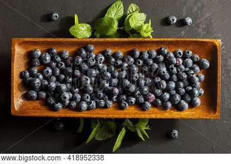 Delicious And Appetizing Blueberry Berries On An Ebony Wood Tray And Mint Leaves (peppermint, Mint).