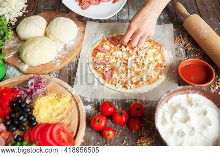 Cook In The Kitchen Putting The Ingredients On The Pizza. Pizza Concept. Production And Delivery Of