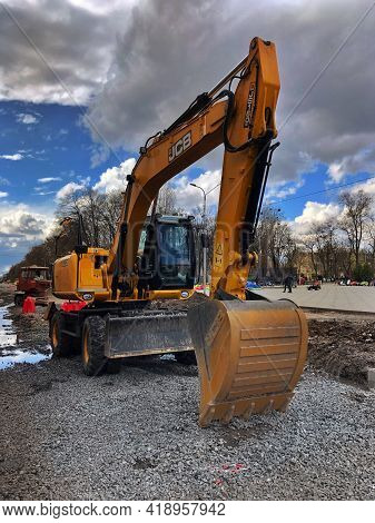 April 24, 2021, Ukraine, Kharkiv, Excavator Work, Road Repair. Construction Machinery Close-up. An E