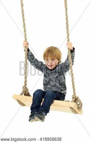 Cute Boy Sitting On Rope Swing. Little Boy Wearing Casual Clothes Having Fun While Swinging On Isola