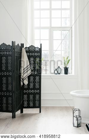 Vertical Shot Of Black Folding Screen With Hanging Towel Near Large Window In Modern And Light Bathr