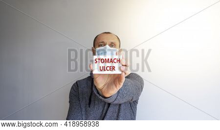 Stomach Ulcer Symbol. White Card With Words 'stomach Ulcer'. A Young Man In A Grey Wear And Medical