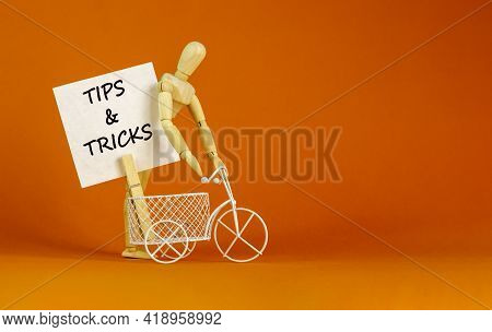 Tips And Tricks Symbol. White Paper. Words 'tips And Tricks'. Miniature Bicycle, Wooden Human. Beaut