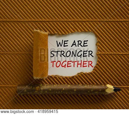 Stronger Together Symbol. Words We Are Stronger Together Appearing Behind Torn Brown Paper. Wooden P