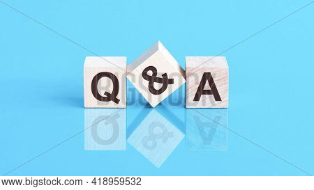 The Text Q And A Written On The Cubes In Black Letters, The Cubes Are Located On A Blue Glass Surfac