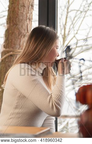 Attractive Young Woman Looking Outside Through A Glass Window And Sipping Coffee. The Tree Trunk Can