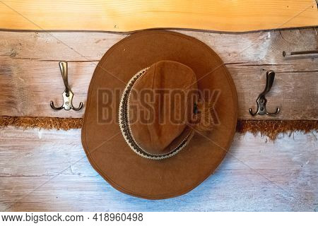 Wall Hanger With A Brown Hat Hanging On It. Wooden Wall Hanger With Metal Hooks. A Nice Cow-bow Hat