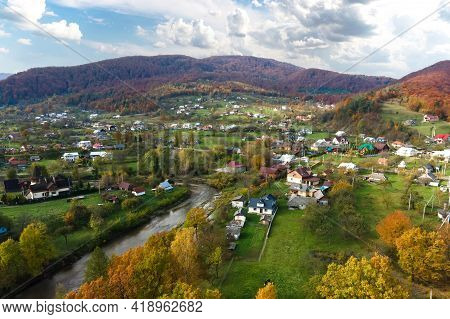 Aerial View Of A Village Rural Area With Small Houses Between Autumn Mountain Hills Covered With Yel
