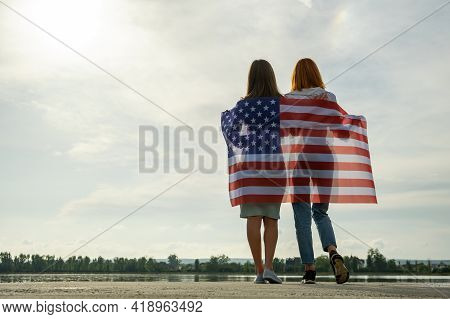 Two Young Friends Women With Usa National Flag On Their Shoulders Standing Together Outdoors On Lake