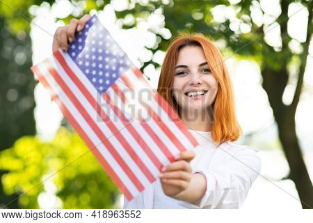 Happy Young Woman Posing With Usa National Flag Outdoors In Summer Park. Pretty Girl Celebrating Uni
