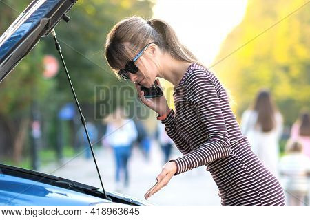 Angry Female Driver Talking On Cell Phone With Assistance Service Worker Standing Near A Broken Car