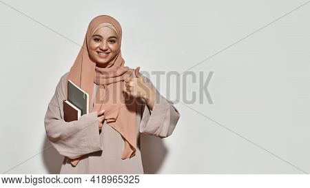 Cheerful Young Arabian Woman Student In Hijab With Notepad Smiling At Camera And Showing Thumb Up Wh