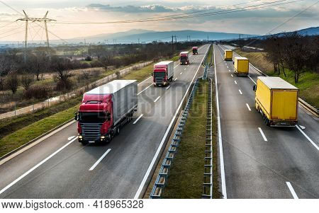 Convoys Or Caravans Of Transportation Trucks Passing On A Highway At Sunset. Highway Transit Transpo
